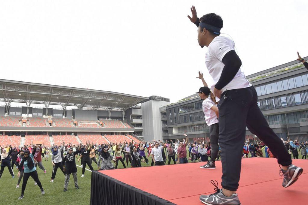 SAMA-SAMA BERZUMBA: Cik Laila (membelakangkan kamera, depan pentas) memimpin salah satu segmen merenggangkan otot bersama para peserta Sihat Berzumba semalam. - Foto BH oleh DIOS VINCOY JR