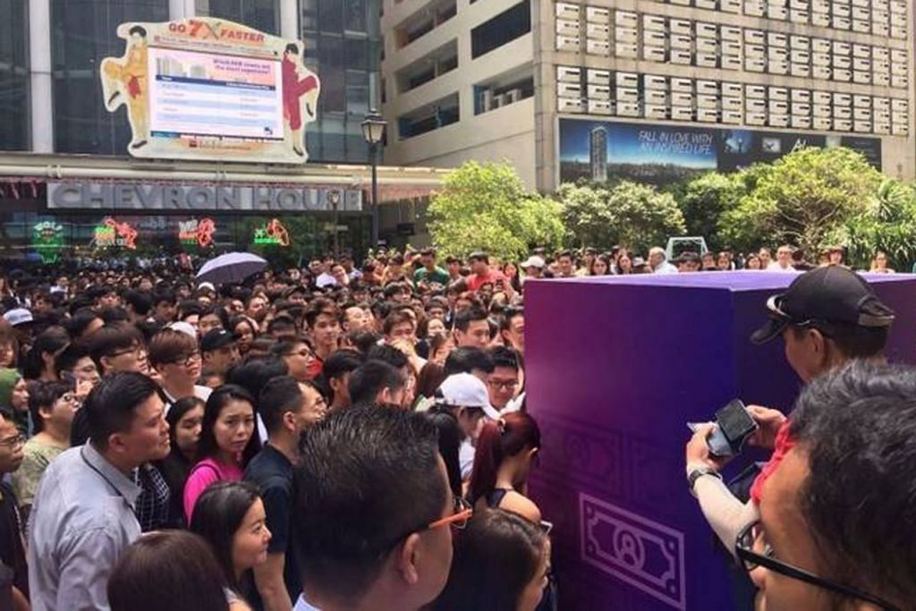 TIMBULKAN TENGKARAH: Promosi duit 'percuma' di Raffles Place tarik beratus-ratus orang hingga berlaku kejadian tolak menolak. - Foto STOMP