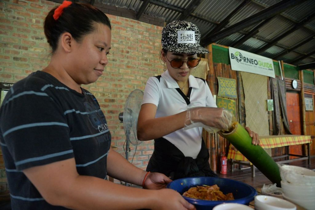 CUBA MASAKAN IBAN: Rosalina Musa (kanan) mempelajari cara memasak lauk Pasuk Manuk atau ayam buluh ketika di Brunei.  - Foto BH oleh FAKHRURADZI ISMAIL