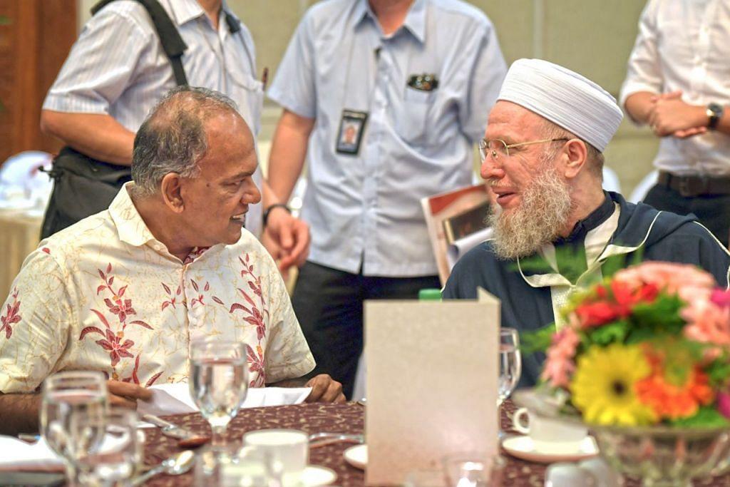 BERSATU DALAM MENENTANG ISIS: Encik Shanmugam (kiri) berbincang dengan Shaykh Sayyid Muhammad Al-Yaqoubi semasa majlis makan tengahari sempena Rahat RRG semalam. – Foto BH oleh ALPHONSUS CHERN