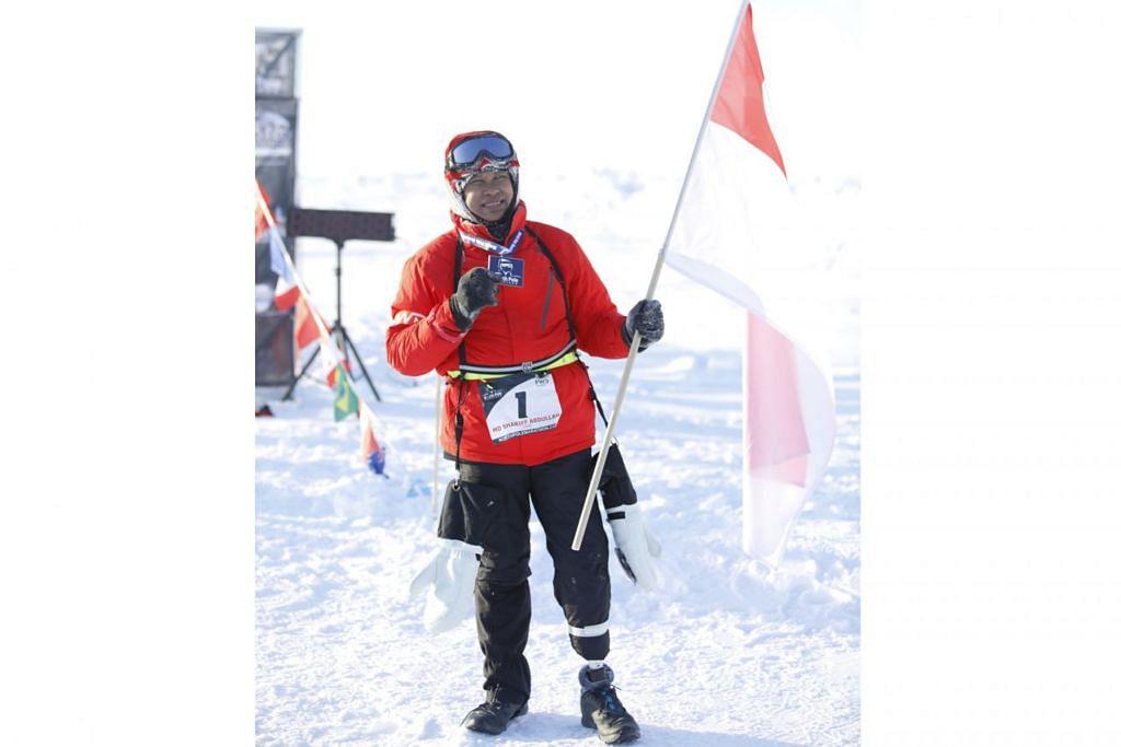 KEBANGGAAN NEGARA: Shariff mengibarkan bendera negara selepas kejayaannya menamatkan separuh Maraton Kutub Utara baru-baru ini. - Foto MARATON KUTUB UTARA FWD