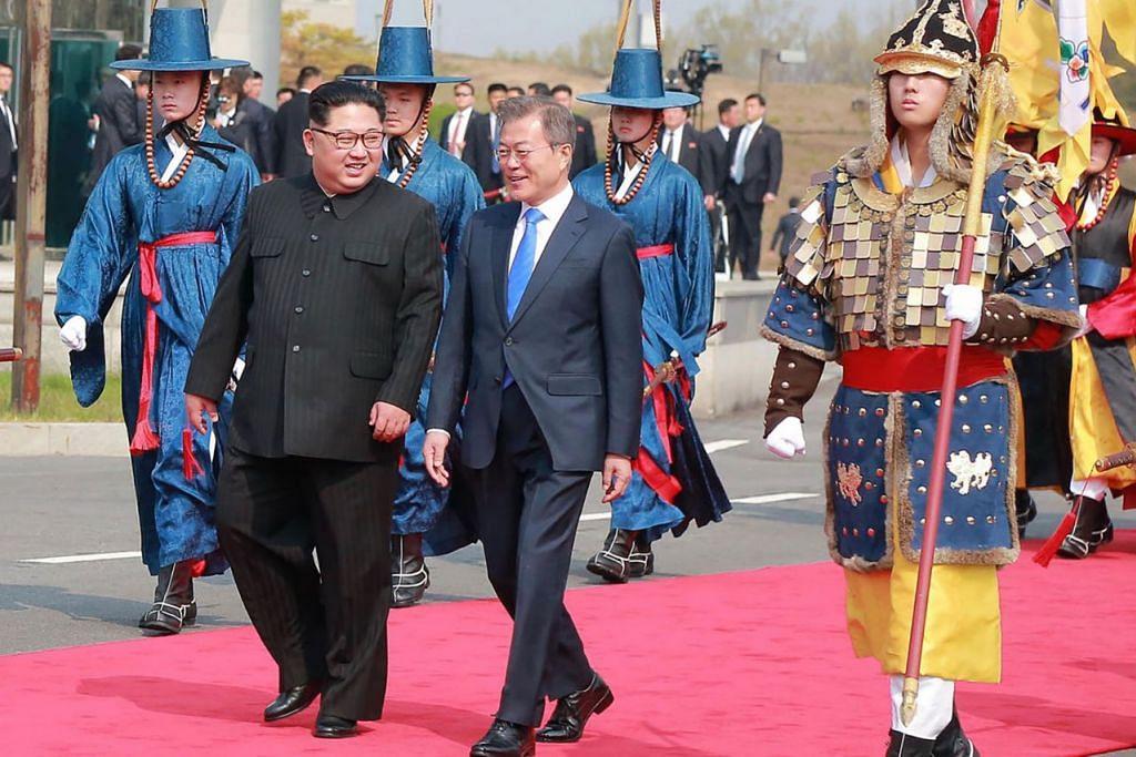 PERTEMUAN BERSEJARAH: Pemimpin Korea Utara Kim Jong Un (kiri) berjalan bersama Presiden Korea Selatan Moon Jae-In selepas bertemu di sempadan yang memisahkan kededua negara bagi menghadiri sidang puncak di bangunan Rumah Kedamaian di Panmunjom. - Foto-foto AFP