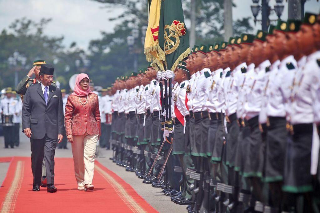 KEHADIRAN DISAMBUT GAH: Sultan Hassanal Bolkiah (kiri) dan Puan Halimah memeriksa barisan kehormatan semasa upacara sambutan yang diadakan di Istana Nurul Iman pagi semalam. – Foto BM oleh GAVIN FOO