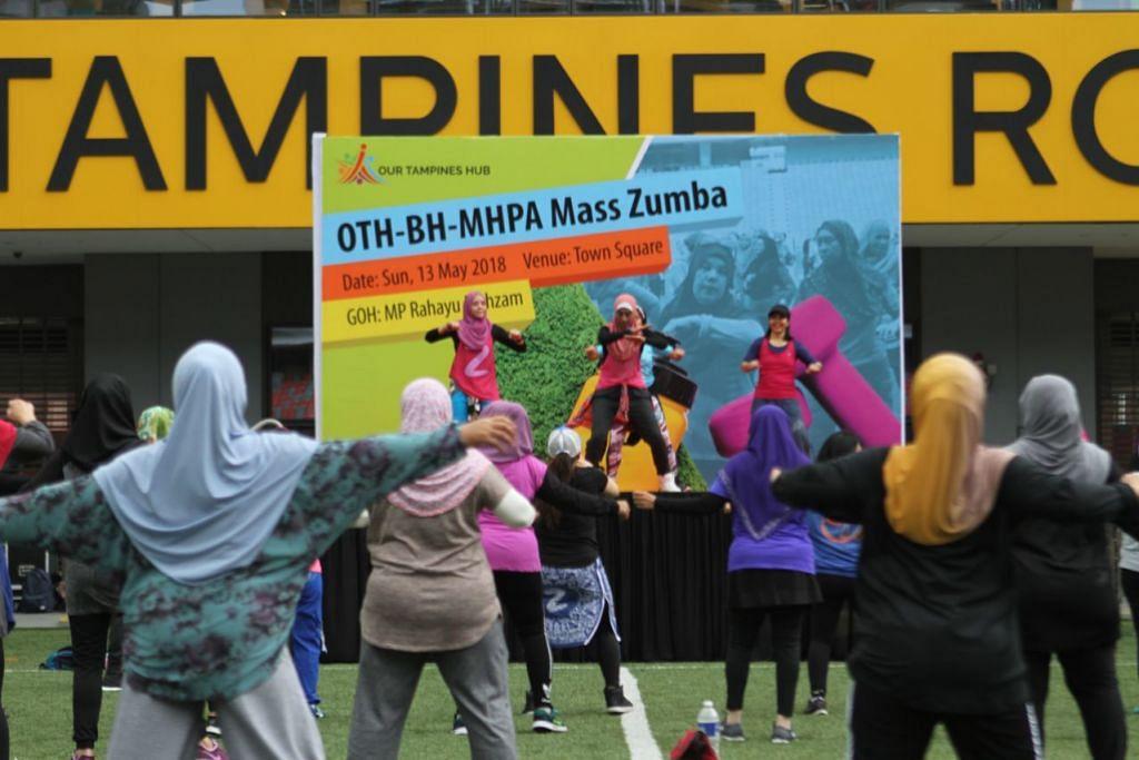SIHAT BERZUMBA: Sekitar 150 orang tetap bersemangat menyertai acara Sihat Berzumba di Our Tampines Hub pagi tadi meskipun hujan.