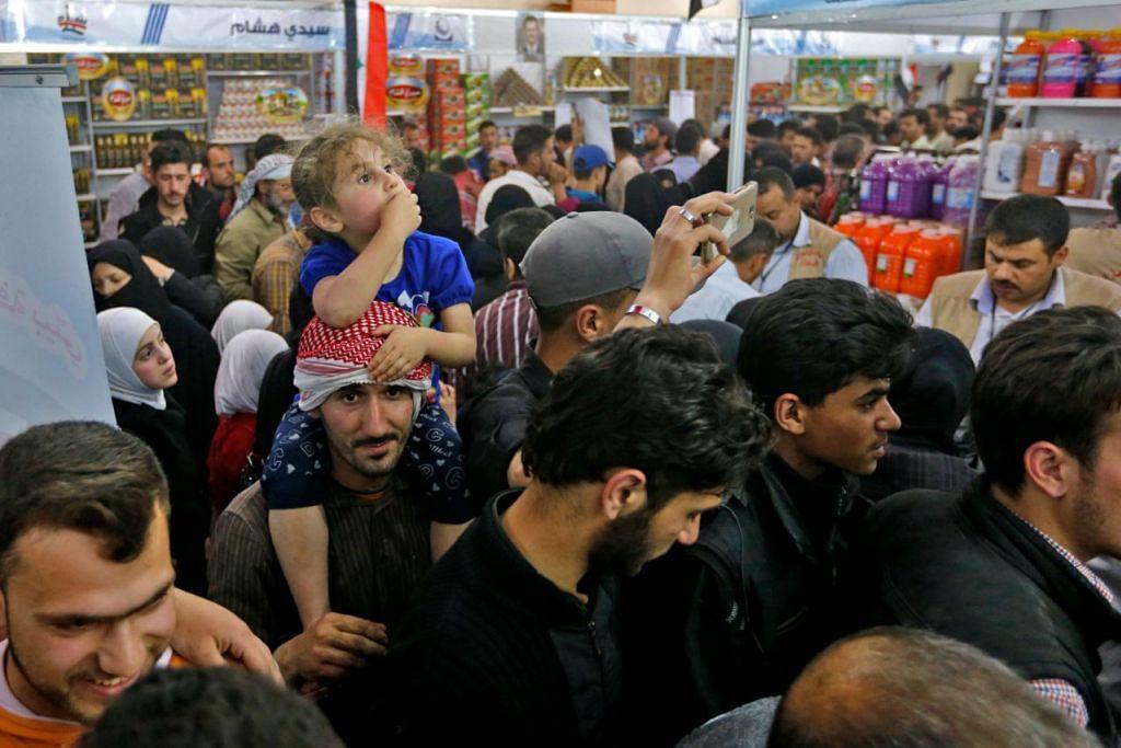 PERUBAHAN: Rakyat Syria berpusu-pusu ke pasar di Douma yang ditaja pemerintah untuk membeli keperluan harian yang dahulu tidak mampu dibeli mereka. Namun keadaan di luar pasar itu belum berubah, dalam kehancuran, dengan kereta terbiar berkarat di luar dan runtuhan bertimbun di jalan-jalan berdebu. - Foto AFP