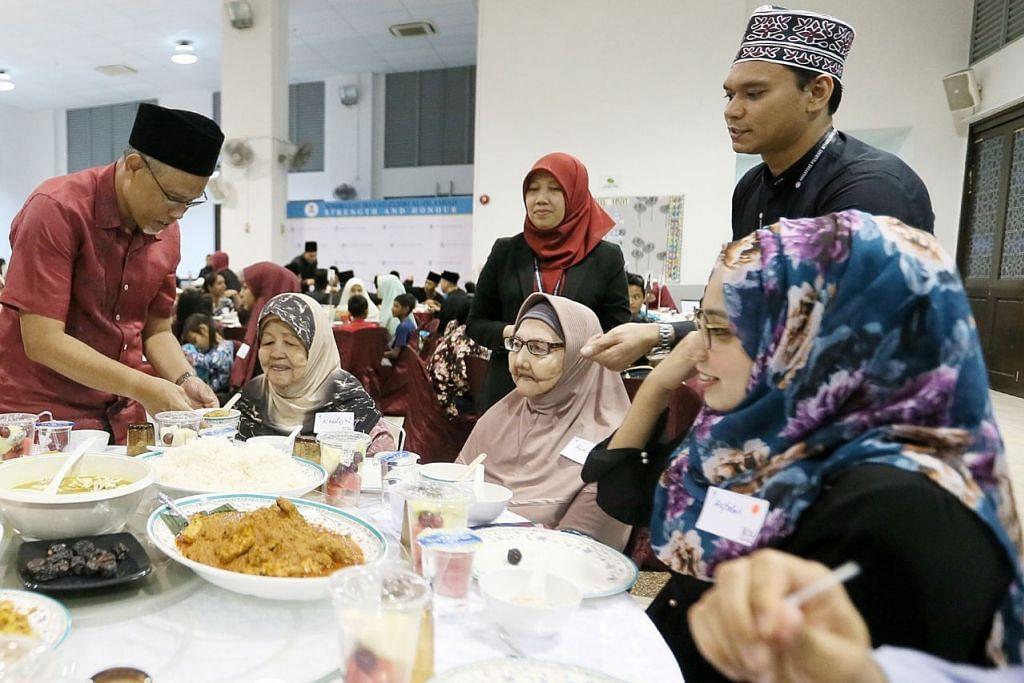 AGIH ZAKAT: Selain mengagihkan zakat, Encik Masagos Zulkifli (kiri) turut menyajikan makanan kepada penghuni Rumah Tumpangan Pertapis dalam acara di Hab Islam Singapura semalam. - Foto BH oleh JONATHAN CHOO