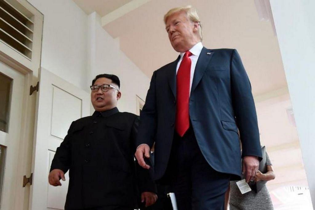 SAAT BERSEJARAH: Encik Trump (kanan) dan Encik Kim berjalan di Hotel Capella, selepas bersemuka buat kali pertama pada 12 Jun.