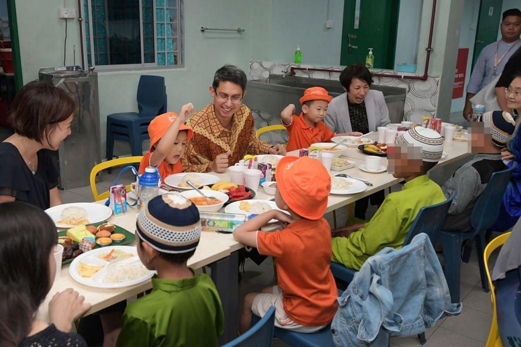 BANTU DARIPADA KECIL: Dr Faishal Ibrahim (tengah, berbaju batik) menyertai sekumpulan kanak-kanak prasekolah dari My First Skool di Blok 612 Yishun berbuka puasa dengan penghuni Rumah Kanak-Kanak Pertapis. Kanak-kanak prasekolah itu telah sama-sama membantu menyiap dan menyajikan makanan bagi acara iftar itu. - Foto BH oleh ALPHONSUS CHERN