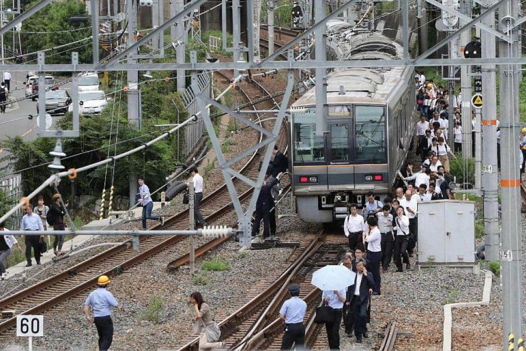 GANGGUAN: Penumpang kereta api terpaksa turun dan berjalan di landasan selepas gempa bumi sekuat 6.1 pada skala Richter melanda Osaka pada 18 Jun 2018.