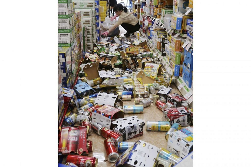 BARANGAN BERTABURAN: Kakitangan di kedai minuman ini cuba mengeluarkan botol dan tin yang berselerak berikutan gempa yang melanda Osaka di wilayah barat Jepun semalam. - Foto REUTERS