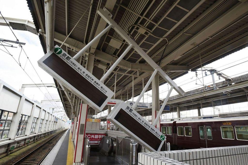 PAPAN PANDUAN IKUT TERJEJAS: Papan elektrik bagi panduan kereta api menjadi miring berikutan gempa bumi di Stesen Ibaraki-shi di Bandar Ibaraki City, utara wilayah Osaka semalam. Tiada laporan segera mengenai kerosakan utama atau risiko tsunami. - Foto AFP