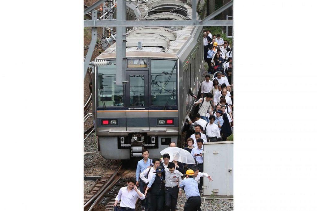 TERPAKSA BERJALAN KAKI: Penumpang berjalan di landasan kereta api di Osaka menyusuli gempa di barat Jepun awal pagi semalam. - Foto AFP