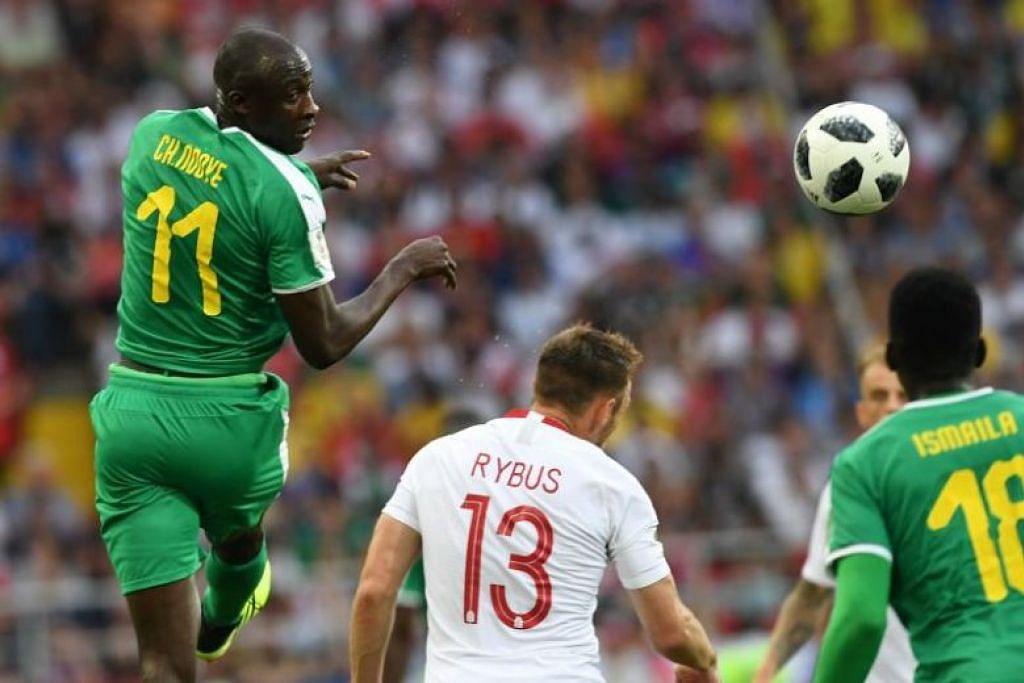 SENEGAL LAWAN POLAND: Pemain midfield Senegal Cheikh Ndoye (kiri) dengan pemain midfield Poland Maciej Rybus semasa perlawanan antara Senegal di Stadium Spartak Stadium.