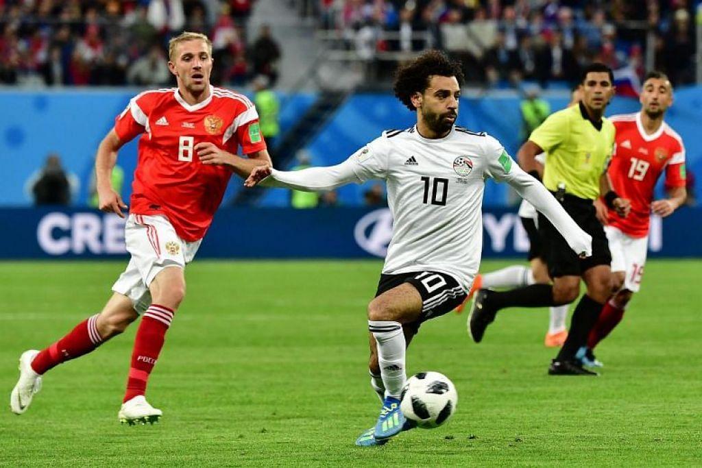 RUSSIA LAWAN MESIR: Mohamed Salah (kanan) dengan pemain midfield Russia Yuri Gazinskiy semasa perlawanan di Stadium Saint Petersburg Stadium.