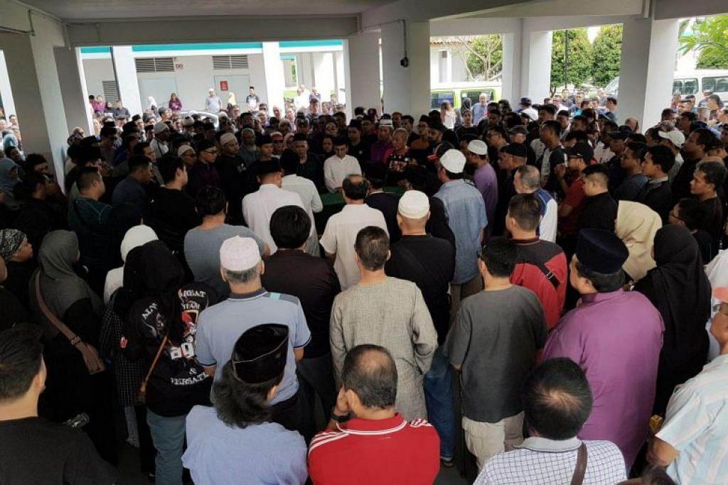 PENGHORMATAN TERAKHIR: Sekitar 200 anggota keluarga dan teman Allahyarham Mohammad Firdaus Jasni hadir untuk memberi penghormatan terakhir kepadanya di flat keluarganya di Jurong West semalam.