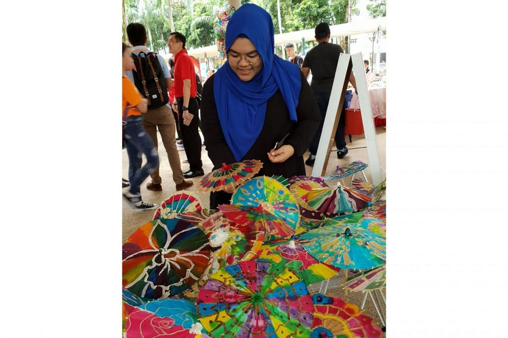 BELI SAMBIL BERAMAL: Cik Nashrah Amirah Mohamed Najib, salah seorang pereka, mencipta acara Payung Batik 1000 dengan payung-payung kecil itu boleh dibeli orang awam. Bagi setiap payung yang dijual, lima kilogram beras akan diberikan kepada orang memerlukan.