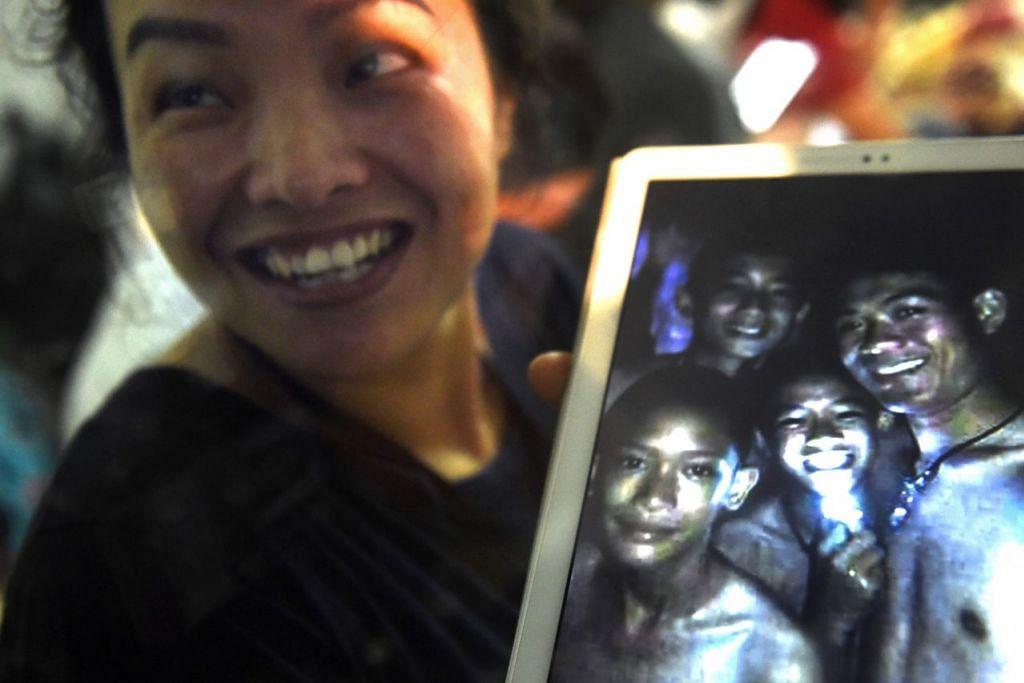 AKHIRNYA DITEMUI: Seorang anggota keluarga menunjukkan gambar empat daripada 12 budak lelaki yang terperangkap dalam gua Tham Luang di Mae Sai bersama jurulatih mereka. Seramai 12 budak lelaki dan jurulatih bola sepak mereka terperangkap yang selama 10 hari, akhirnya ditemui lewat kelmarin. - Foto AFP