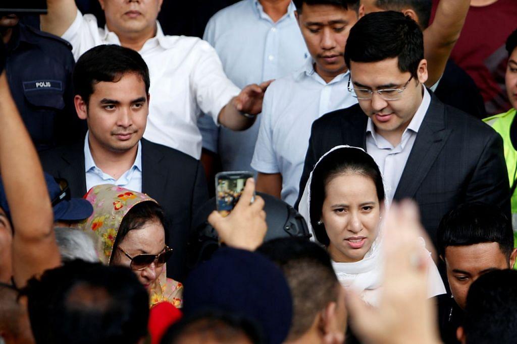 HADIR DI MAHKAMAH: Anak mantan perdana menteri Datuk Seri Najib Razak, Cik Nooryana Najwa Najib (bertudung putih menghadap kamera), hadir bersama suami; Encik Daniyar Nazarbayev (bercermin mata); adiknya, Encik Norashman Najib; dan ibunya, Datin Seri Rosmah Mansor (bercermin mata gelap) dikerumuni pihak media di perkarangan mahkamah semalam. - Foto REUTERS