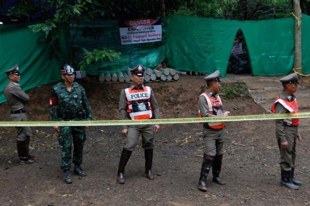 KEADAAN GENTING: Pegawai polis dan kakitangan keselamatan mengawal kawasan mulut gua Tham Luang.