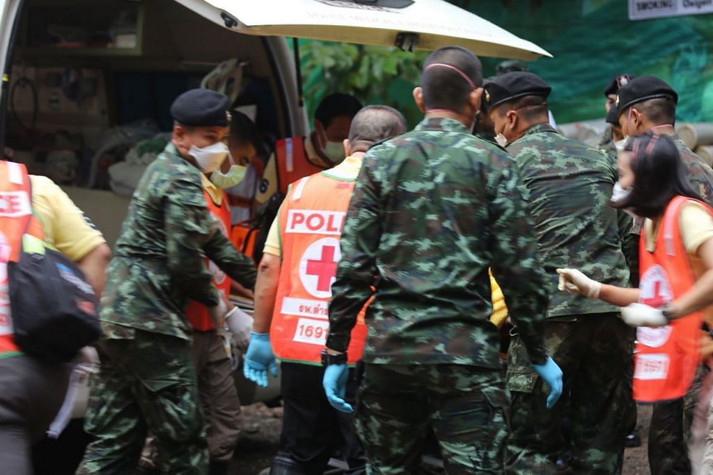 SELAMAT: Gambar yang diambil dan diedarkan oleh Pejabat Perhubungan Awam Chiang Rai menunjukkan askar dan paramedik Thai membantu seorang budak yang diselamatkan dari gua Tham Luang kelmarin masuk ke dalam ambulans bagi dikejarkan ke hospital. - Foto AFP