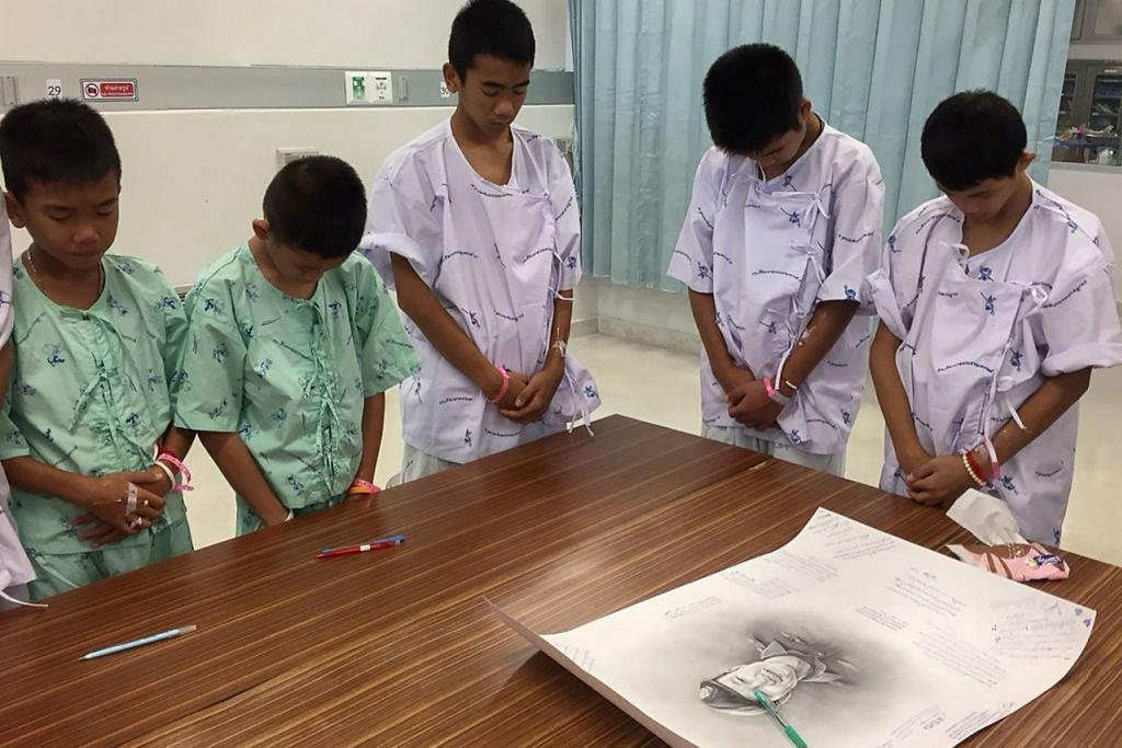 KENANG JASA PENYELAMAT TERKORBAN: Sebahagian anggota pasukan bola sepak Wild Boars yang diselamatkan dan sedang menjalani rawatan di Hospital Prachanukroh bertafakur bagi mengenang jasa seorang penyelamat, mendiang Samarn Kunan, (wajah yang dilukis, atas meja), yang maut semasa menjalankan usaha menyelamat 12 remaja itu dan seorang jurulatih mereka. - Foto REUTERS