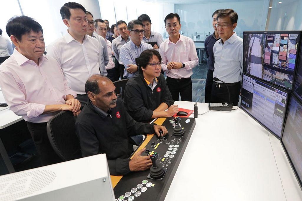 TEKNOLOGI CANGGIH: Encik Khaw (kiri) dan Menteri Negara Kanan (Pengangkutan dan Kesihatan), Dr Lam Pin Min (dua dari kiri) melawat Pusat Operasi Kren Automatik semalam. Sistem kawalan Pusat Operasi Kren Automatik itu boleh menggerakkan kontena dari kapal yang berlabuh di Terminal Pasir Panjang ke lori kontena dengan lebih pantas. - Foto BH oleh KELVIN CHNG