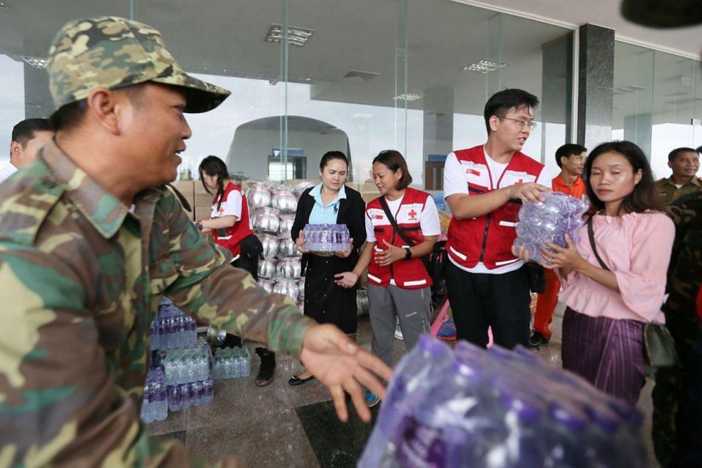 HULUR BANTUAN: Pasukan Palang Merah Singapura yang memakai jaket merah (dari kiri) Cik Jacqueline Ng, Cik Geraldine Aggarao dan Encik Samuel Lee membantu menyusun bekalan yang dibawa mereka termasuk air botol, mi segera, makanan dalam tin dan sebagainya. - Foto-foto BH oleh JONATHAN CHOO KK