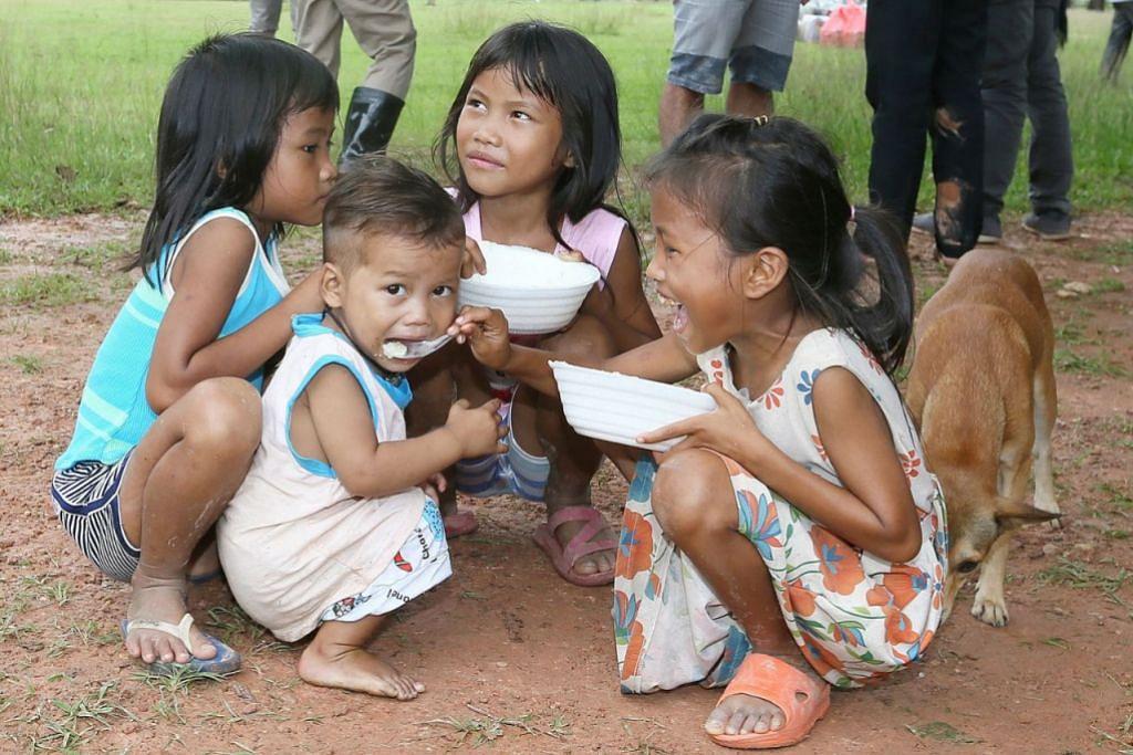 BANTUAN MAKANAN: Kanak-kanak menikmati bubur di pusat pemindahan Sanamxay.