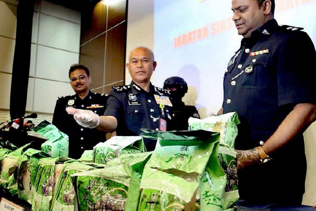 MINUMAN 'TERCEMAR': Pengarah Jabatan Siasatan Jenayah Narkotik Bukit Aman, Pesuruhjaya Datuk Seri Mohmad Salleh (tengah), menunjukkan sampel-sampel minuman yang telah dicemari dengan dadah. - Foto NST
