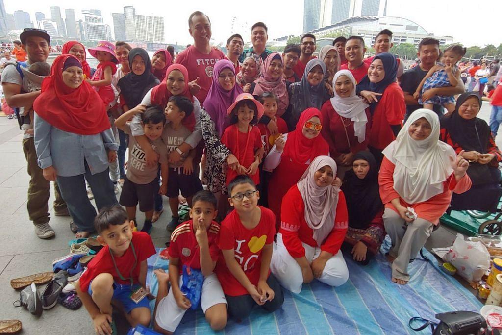 BERKUMPUL UNTUK NEGARA: Cik Noraini (bertudung biru) bersama 40 anggota keluarganya memeriahkan lagi suasana di sekitar Marina Bay. - Foto BH oleh NUR HUMAIRA SAJAT