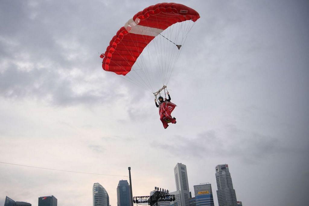 AKSI MENDEBARKAN: Seorang anggota kumpulan The Red Lions melakukan aksi terbang masuk ke Pentas Terapung Marina Bay dengan tepukan gemuruh penonton. - Foto BH oleh MARK CHEONG
