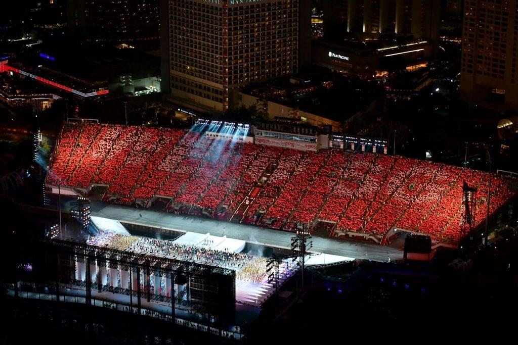 "PENONTON TERLIBAT SAMA: Penonton di pentas terapung mengangkat plakad mereka bagi membentuk perkataan ""We Love Singapore"" dalam salah satu segmen persembahan. - Foto BH oleh LIM YAOHUI"