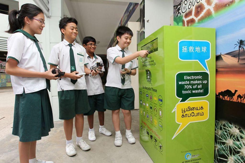 KITAR SEMULA: Para pelajar membuang barangan elektronik yang tidak digunakan lagi ke dalam tong kitar semula yang disediakan di bawah Program 'RENEW' StarHub. - Foto fail