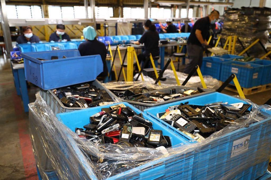 JALANI PROSES RUMIT DIKITAR SEMULA: Para pekerja tekun menjalankan tugas di sebuah pusat pembuangan e-sampah yang terletak di kawasan Jurong. Satu kajian NEA baru-baru ini mendapati sehingga 11 kilogram e-sampah - yang sama dengan timbangan sekitar 73 telefon bimbit - dibuang oleh setiap orang di negara ini setiap tahun.