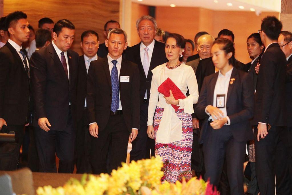 BERI CERAMAH: Cik Aung San Suu Kyi tiba bagi menyampaikan Ceramah Singapura ke-43 di Hotel Grand Hyatt semalam. Bersamanya juga ialah DPM Teo (lima dari kiri). - Foto BH oleh KELVIN CHNG