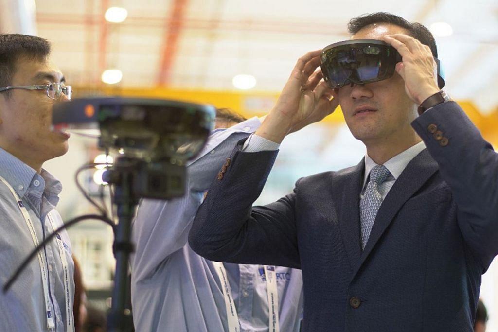KE ARAH TEKNOLOGI PERKILANGAN LANJUTAN: Dr Koh (kanan) menggunakan lensa realiti terimbuh bagi melihat cara pengilangan tradisional dirombak menjadi sistem fleksibel yang menggunakan teknologi canggih. - Foto MTI