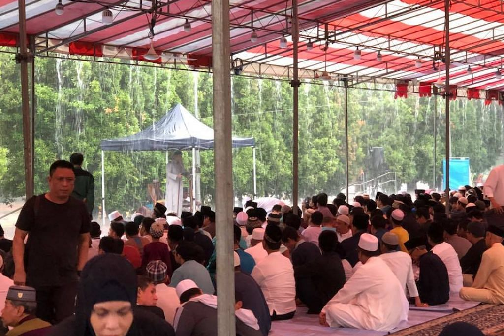 Muslims perform Eid prayers while keeping dry under tentage built by Shen Fu Gong Temple despite heavy rain