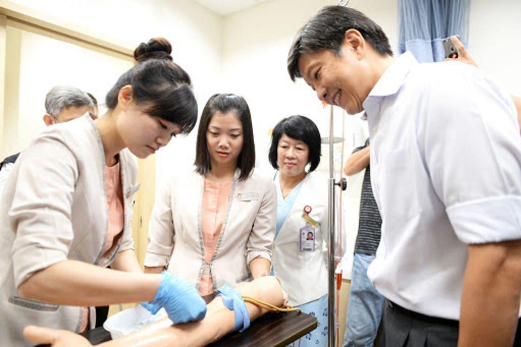 PERANAN LEBIH LUAS: Encik Ng menyaksikan prosedur mengambil darah yang ditunjukkan pegawai kanan khidmat pesakit, Cik Woon Shi Mei (paling kiri).  Foto Matthias Chong
