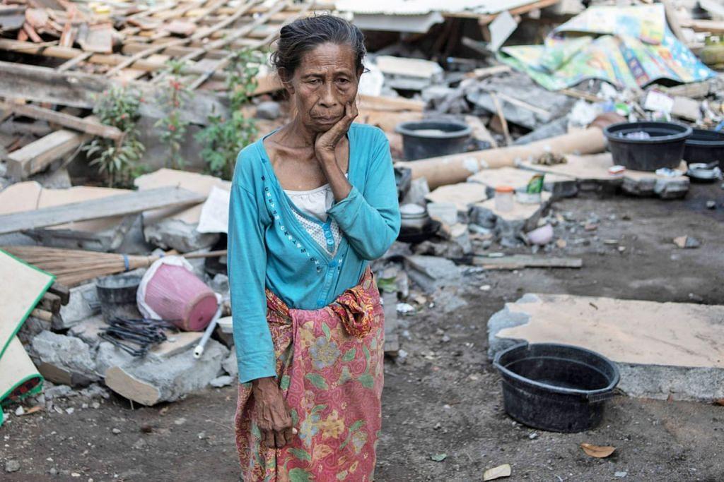 SUGUL: Seorang penduduk kampung Labu Pandan mengenangkan nasib memandangkan rumahnya habis ranap ekoran gempa yang melanda Lombok baru-baru ini. - Foto AFP
