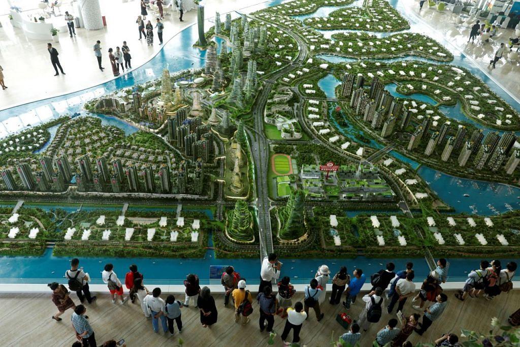 TIMBUL PERCANGGAHAN?: Bakal pembeli melihat model pembangunan Country Garden Forest City Johor Bahru di bilik pameran tahun lalu. - Foto REUTERS