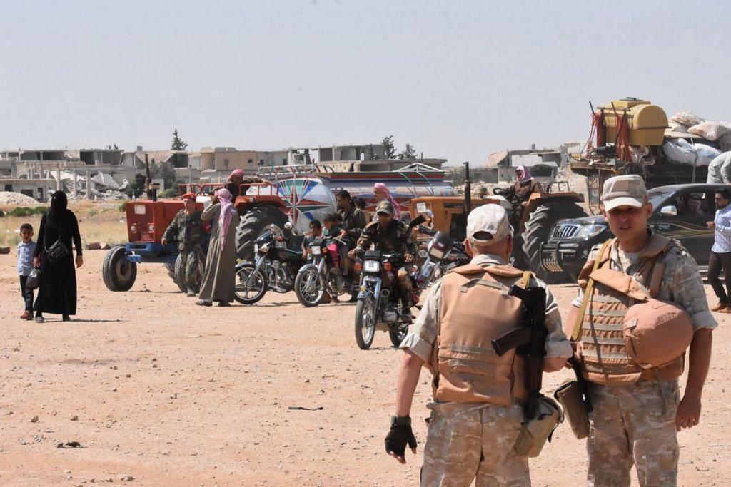 DIJANGKA LANCAR SERANGAN: Tentera Syria dan Russia berkawal di Abu Duhur, di pinggir timur wilayah Idlib, sedang penduduk kembali ke kampung mereka yang dirampas semula oleh pasukan rejim daripada pemberontak. Askar Syria dijangka melancarkan serangan besar-besaran ke atas Idlib untuk merampas semula keseluruhan wilayah itu. - Foto AFP
