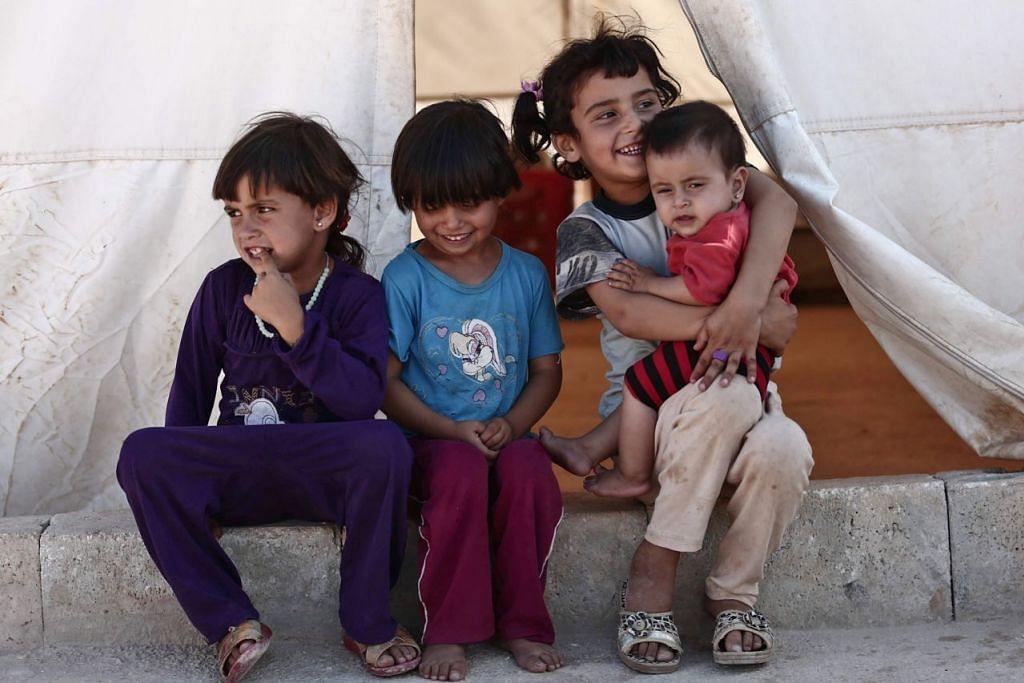 MASIH TERSENYUM: Kanak-kanak ini yang berada di khemah wilayah Idlib mungkin tidak tahu nyawa penduduk di hujung tanduk.   - Foto AFP
