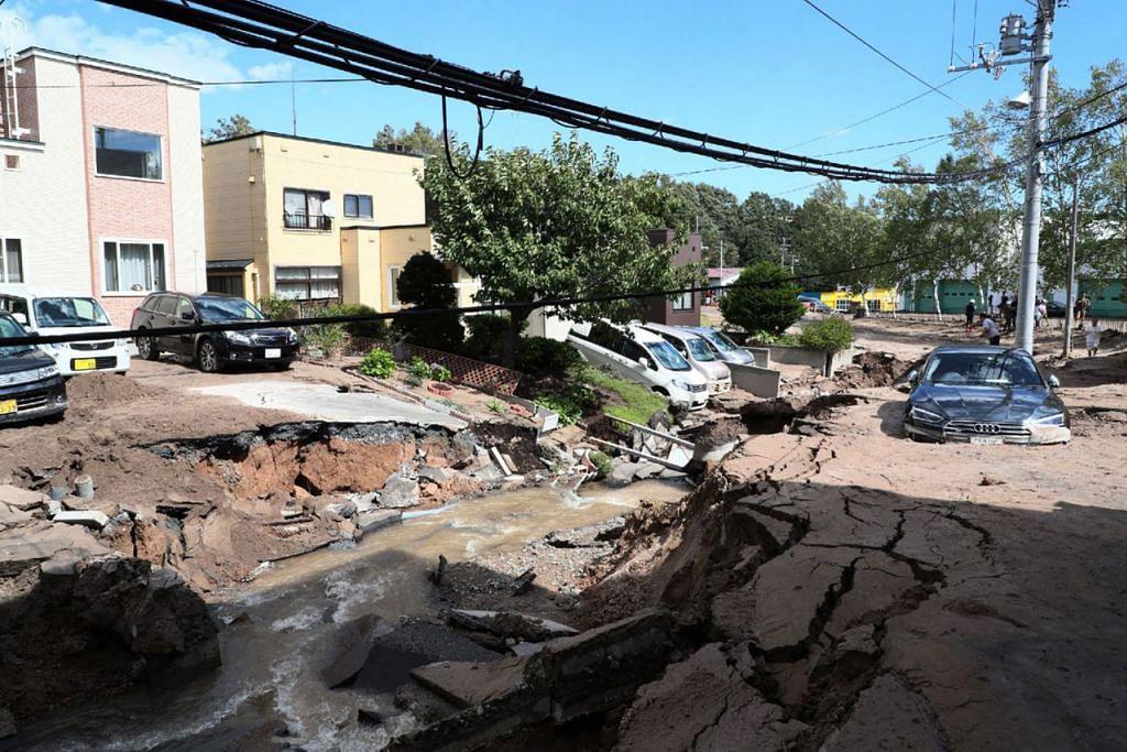 KERETA TERKANDAS: Jalan raya di Sapporo, Hokkaido, ini merekah ekoran gempa bumi kuat yang melanda semalam. - Foto AFP