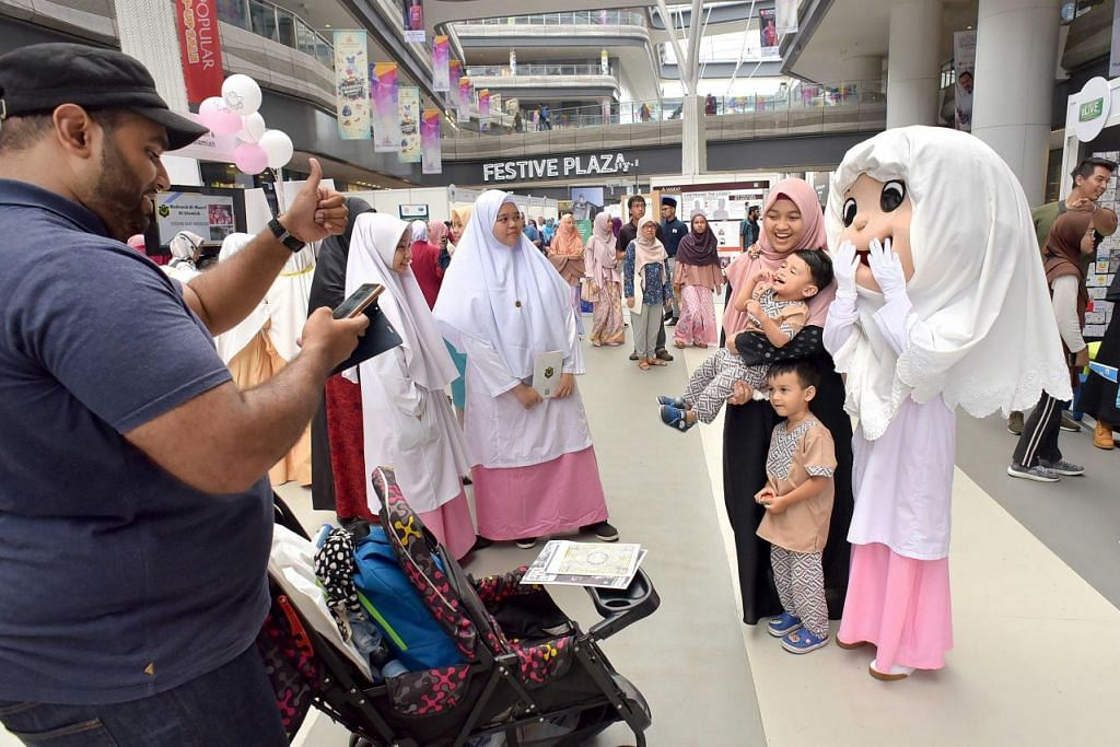 MENDEKATI MASYARAKAT: Para pengunjung tidak melepaskan peluang bergambar dengan maskot pelajar Madrasah Al-Maarif Al-Islamiah di acara Salam Singapore. – Foto BH oleh LIM SIN THAI