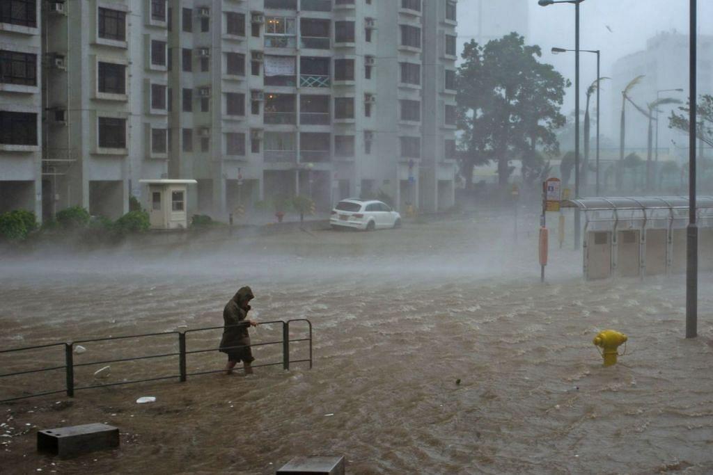 'LAWAN' BANJIR: Seorang lelaki ini cuba melintasi jalan yang dipenuhi air banjir di wilayah pesisir Heng Fa Chuen di Hongkong yang dicetuskan Taufan Mangkhut (gambar atas).  - Foto AFP