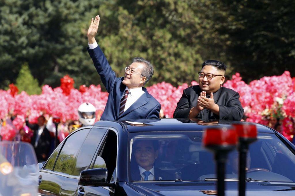 SIDANG: Pemimpin Korea Utara Kim Jong Un (kanan) and Presiden Korea Selatan Moon Jae-in (kiri) melambai kepada penduduk Pyongyang. Kededua pemimpin mengadakan sidang di ibu negara Korea Utara itu. - Foto AFP
