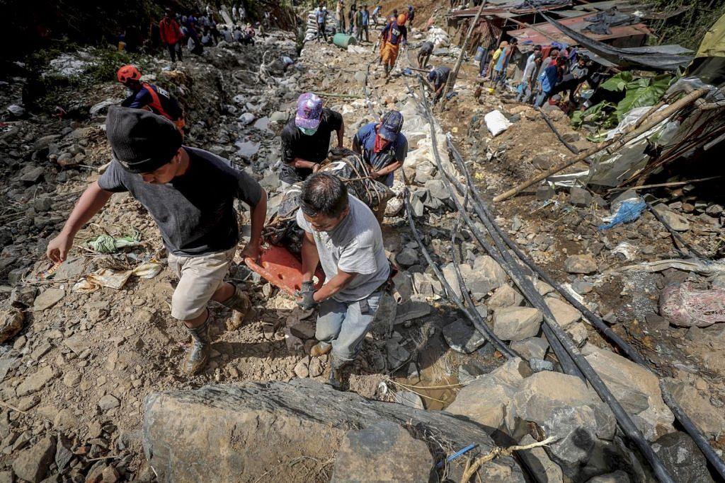MANGSA MANGKHUT: Penduduk Filipina membawa mayat seorang mangsa yang terkorban akibat tanah runtuh semasa taufan Mangkhut melanda kampong Ucah di bandar Itogon, Provinsi Benguet. - Foto EPA