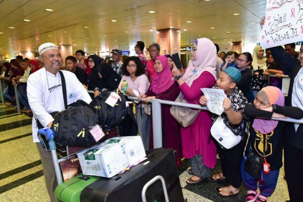 SELAMAT PULANG: Anggota keluarga bersyukur menyambut kepulangan anggota keluarga yang pulang dari menunaikan ibadah haji. - Foto MUIS