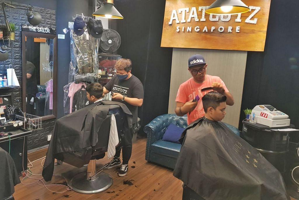 GUNTING AMAL: Encik Effendy Ali (kanan, berbaju warna jingga) menggunting rambut pelanggan di kedai gunting lelaki Atatcutz Singapore di Simpang Bedok. Beliau membuka kedai itu November lalu dan sejak itu telah menyertai beberapa acara gunting rambut amal buat golongan berpendapatan rendah. - Foto ATATCUTZ SINGAPORE