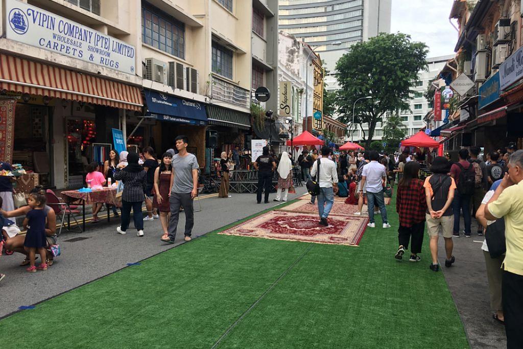 SUASANA SANTAI: Hambal dan permaidani dibentangkan di jalan raya di Arab Street untuk orang ramai bersantai sambil menikmati pelbagai persembahan di jalanan. - Foto BH oleh HANIM MOHD SALEH